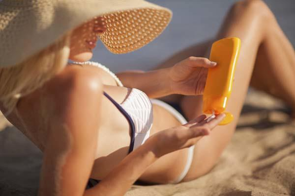 woman applies suntan lotion bikini body